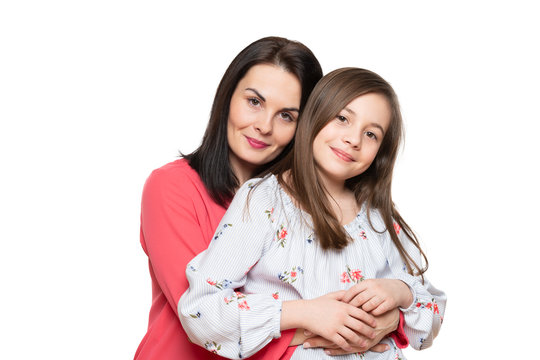 Waist up studio portrait of cute and playful schoolgirl embracing her mother. Happy smiling family background isolated over white background.