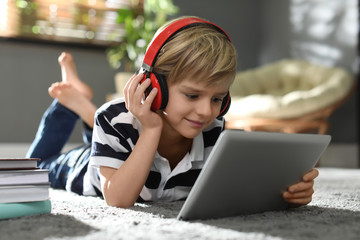 Cute little boy with headphones and tablet listening to audiobook at home Fototapete