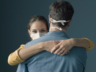 Millennials couple wearing a protective mask and hugging