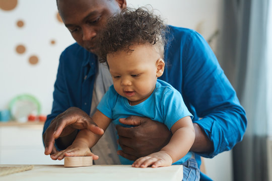 Portrait of cute African-American toddler playing with wooden toys together with dad, copy space