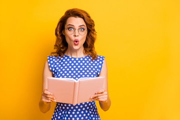 Photo of beautiful shocked lady hold novel book hands open mouth not believe intrigue ending wear specs polka-dot blue white shirt isolated yellow color background