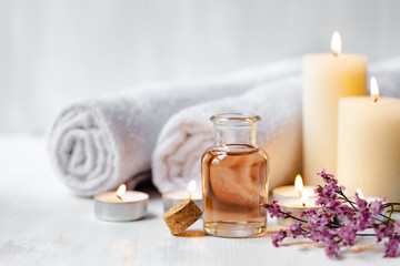 Foto auf AluDibond Spa Concept of spa treatment in salon. Natural organic oil, towel, candles as decor. Atmosphere of relax, serenity and pleasure. Anti-stress and detox procedure. Luxury lifestyle. White wooden background