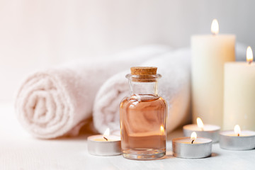 Fotorollo Spa Concept of spa treatment in salon. Natural organic oil, towel, candles as decor. Atmosphere of relax, serenity and pleasure. Anti-stress and detox procedure. Luxury lifestyle. White wooden background