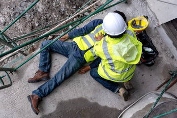 First aid support accident at work of construction worker at site. Builder accident falls scaffolding on floor, Safety team helps employee accident.