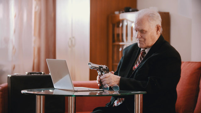 An old man sitting by the laptop and holding a gun