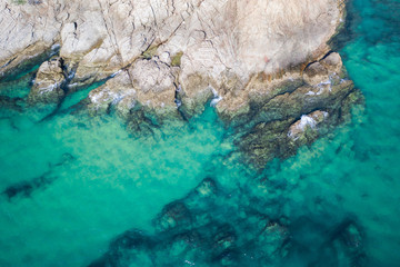 Canvas Prints Turquoise Aerial drone top view of turquoise sea surface with stones and rocks in water