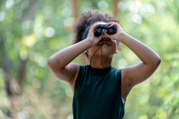 Little African American Girl with Binoculars during Hiking in Forest.