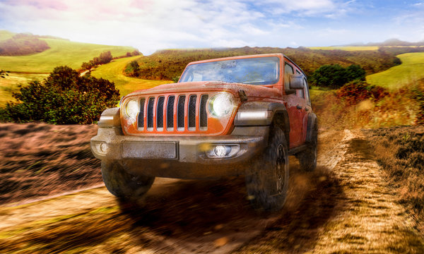 All terrain vehicle JEEP Wrangler Rubicon driving the dirt track in landscape panorama