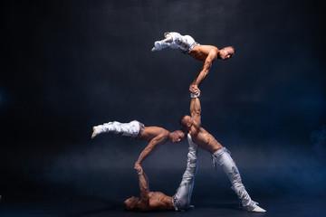 Four muscular man perform difficult acrobatic tricks on black studio