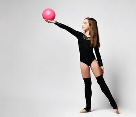 girl gymnast trains with a gymnastic ball . children's professional sports. rhythmic gymnastics.
