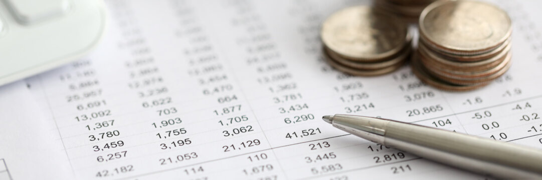 Silver pen lying over financial statistics paper with set of numbers