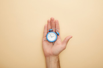 Fototapeta cropped view of man holding small alarm clock on beige background