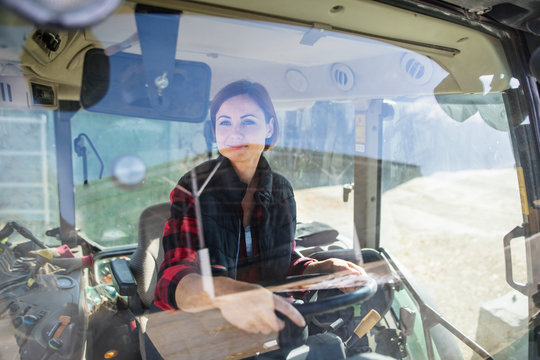Woman worker riding tractor on diary farm, agriculture industry.