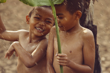 Asian boys are happy because they play in the rain. After a long drought.