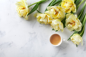 Morning coffee and beautiful bunch of tulip flowers on white stone table top view. Flat lay style. Cozy breakfast on Mother or Woman day.