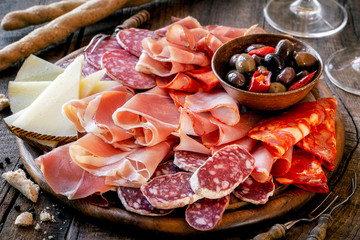 Cures meat platter with cheese and spicy olives served as traditional Spanish tapas on a wooden board. Selection of ham, salami and goat cheese Fotomurales