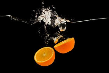 Falling citrus fruits. Orange halves splattering into water on black background Wall mural