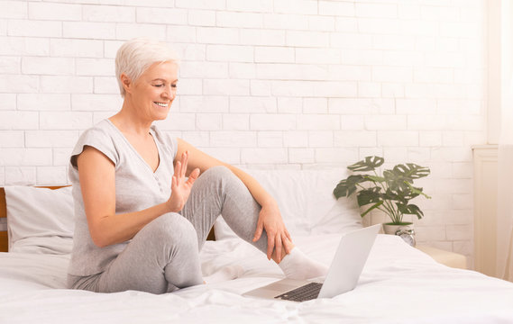 Cheerful senior lady talking with friends on laptop online
