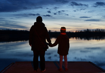 A adult and a child standing on a pier and watching into the evening sky