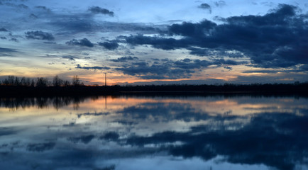 Beautiful evening landscape with reflection of clouds in a lake