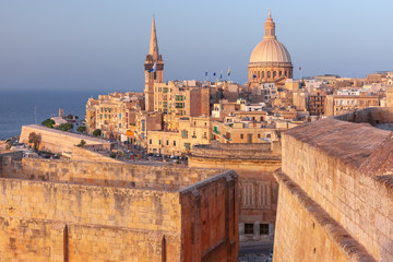 Fototapete - View of Old town roofs, fortress, Our Lady of Mount Carmel church and St. Paul's Anglican Pro-Cathedral at sunset , Valletta, Capital city of Malta