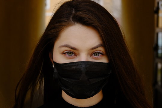 Girl, young woman in protective sterile medical mask on her face looking at camera outdoors close up.  Corona virus pandemic. Beautiful brunette haired girl with medical mask.