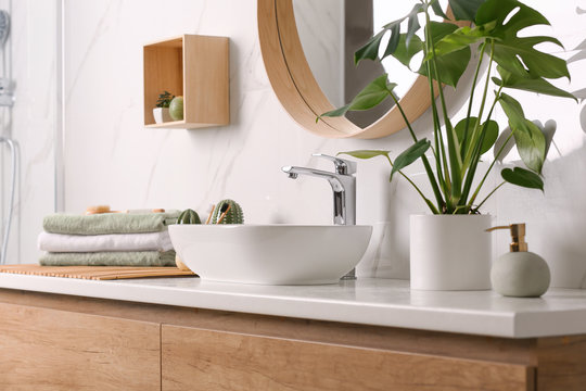 Stylish vessel sink on light countertop in modern bathroom