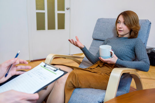 Young woman at the office of a psychologist at a consultation. A session with a psychotherapist.