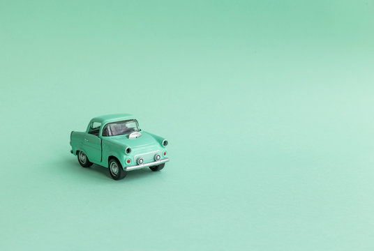 Mint toy car on  the road on a neo mint background
