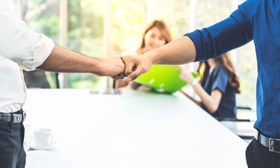 Close up images, the hand of Business men Fist bump with blurred of business women meeting at workplace, concept to business teamwork for success