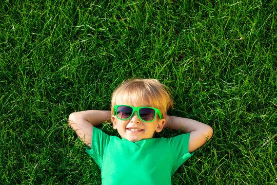 Happy child lying on spring green grass