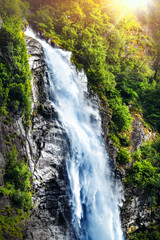 Printed roller blinds Waterfalls Panoramic beautiful deep forest waterfall in norway near blue ocean. Waterfalls mountain view close up.
