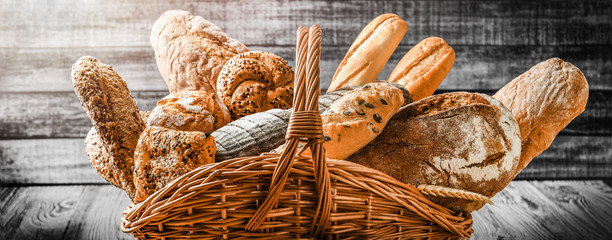Various bread with wheat on old table in wooden wicker basket. Bakery food concept panorama or wide banner baker's ware photo.