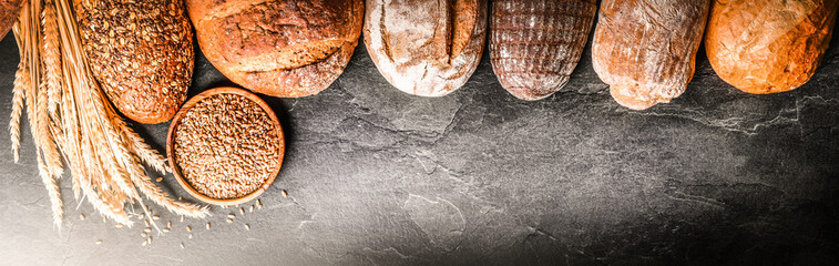 Bread with wheat and bowl of flour on dark board, White bakery food concept panorama or wide banner photo.