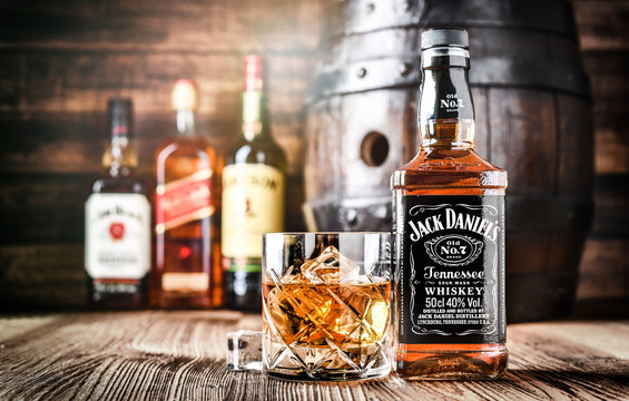 VAVRISOVO, SLOVAKIA - SEPTEMBER 14, 2019: Famous whiskey bottles and whisky barrel, The most popular liquor in the world. Alcohol drink concept.
