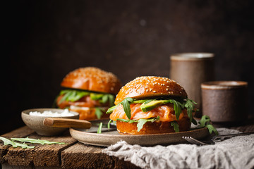 Foto op Canvas Snack Burger sandwich with salmon, cream cheese, avocado and arugula on a light background, concept diet food, take away, healthy fast food