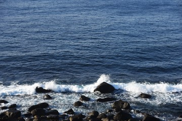 Winter Seascape / Blue sea and white waves breaking on rocks.