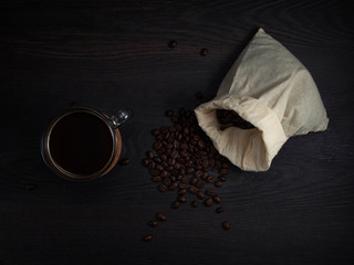 Wall Murals Cafe glass mug with fresh black natural coffee, a bag with coffee grains and sprinkled grains of roasted coffee on a wooden table