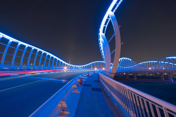 Meydan Bridge and street road or path way on highway with modern architecture buildings in Dubai Downtown at night, urban city at night, United Arab Emirates or UAE. Wall mural