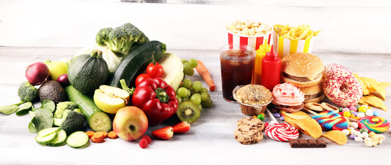 Fototapeta healthy or unhealthy food. Concept photo of healthy and unhealthy food. Fruits and vegetables vs donuts,sweets and burgers obraz