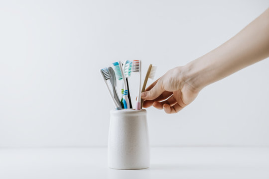 Hand takes eco friendly toothbrush from a white cup. White background with space for text. Dental care concept