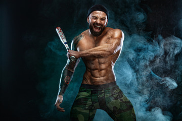 Strong and fit man bodybuilder with baseball bat shows abdominal muscles under a t-shirt. Sporty muscular guy athlete. Sport and fitness concept. Men's fashion.