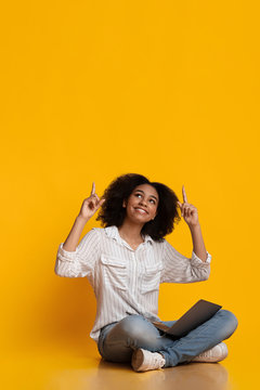 Excited black woman sitting with laptop on floor and pointing upwards