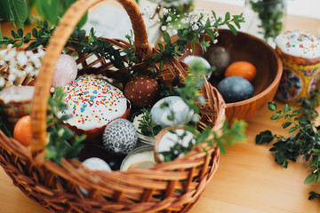 Traditional Easter basket. Easter modern eggs, easter bread, ham, beets, butter, in wicker basket decorated with green boxwood branches and flowers on rustic wooden table