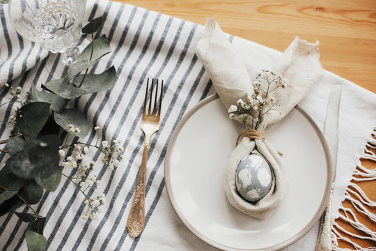 Easter table decorations. Stylish Easter brunch table setting with egg in easter bunny napkin. Modern natural dyed blue egg on napkin with bunny ears, flowers on plate and vintage cutlery.