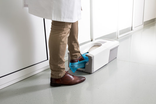 Doctor putting protective shoes on in laboratory