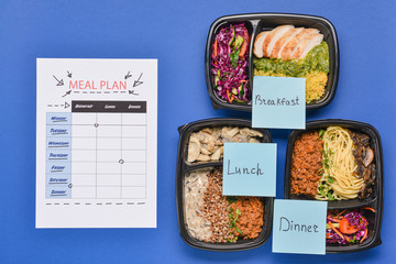 Containers with healthy food and meal plan on color background