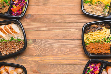 Containers with healthy food on wooden background