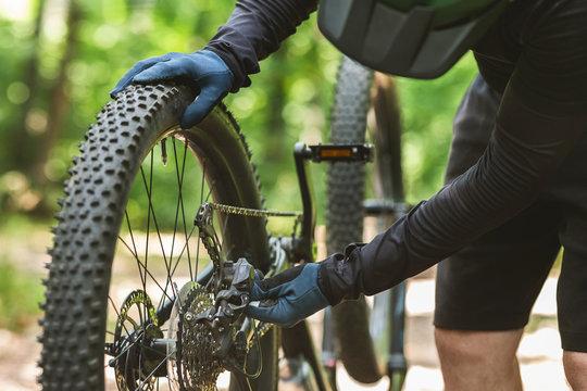 Handy sportsman fixing his bike during riding