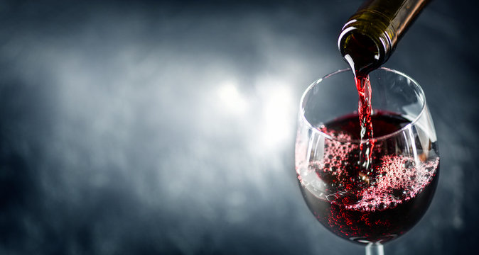 Pouring glass of red wine from a bottle in wide banner shape or copy space for text